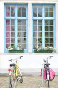 bicycles-white-house-blue-windows-two-parked-front-49009417
