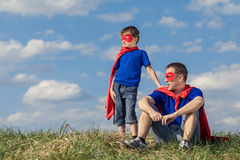padre-e-hijo-que-juegan-al-super-héroe-en-el-tiempo-del-día-93023696