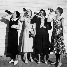 ca. 1925 --- Four women line up along a wall and chug bottles of liquor in the 1920s. --- Image by © Kirn Vintage Stock/Corbis